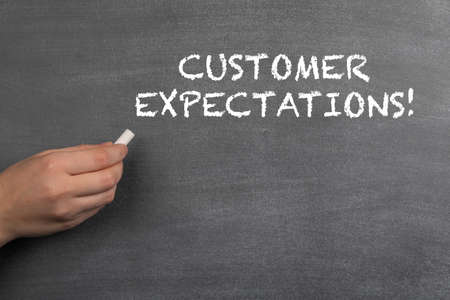 CUSTOMER EXPECTATIONS. White chalk in a womans hand. Black chalk board