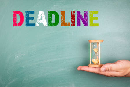 DEADLINE. Time management and business concept. Hourglass in hand. Green blackboard