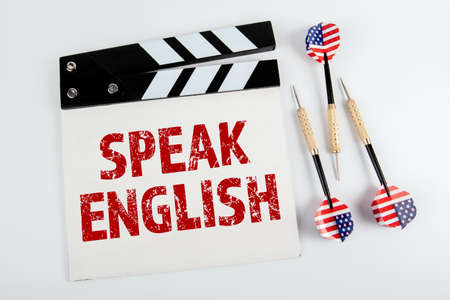 SPEAK ENGLISH. Movie clapper and three darts with the American flag