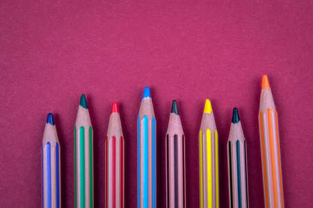 Colored pencils on a red background. Free text space for advertising and marketing Stock Photo