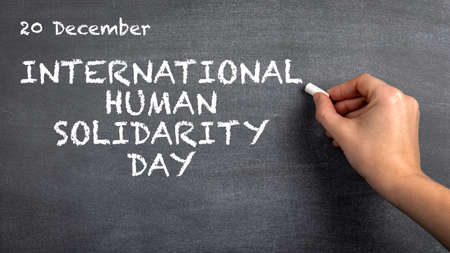 International Human Solidarity Day, 20 December. Womans hand with white chalk