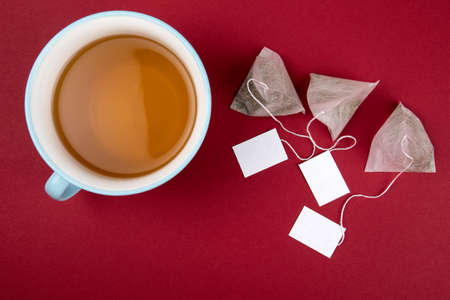 Teabags with label. Top view, on a red background. Mockup