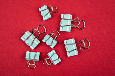 Binder paper clips on a red background. Office supplies Stock Photo