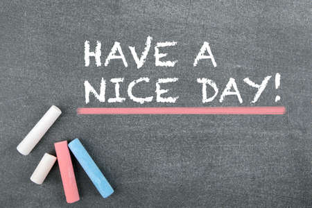Have a nice day. Greetings, inspiration and good wishes. Gray chalk board background Stock Photo