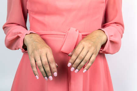 Woman with a pink dress and pink lacquered nails. Beauty, fashion and health