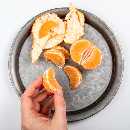 Peeled tangerine fruit and a womans hand. Mandarin pieces on a metal plate