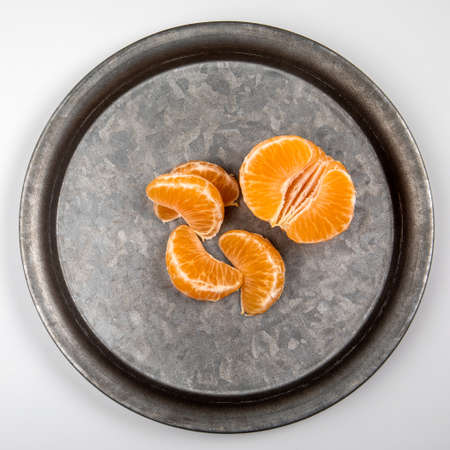 Peeled tangerine fruit, Mandarin pieces on a metal plate