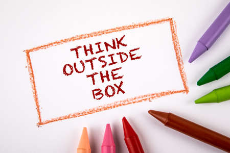 Think outside the box. Colored crayons on a white sheet of paper