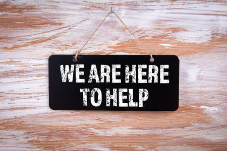 We Are Here To Help. Chalk board hung on a wooden wall