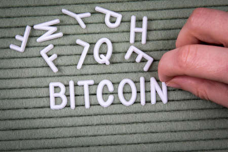 BITCOIN. Cryptocurrency, finance and profit concept. White letters of the alphabet with a womans hand