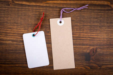 Cardboard and white paper price tags on a wooden texture background