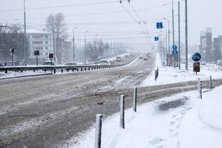 Traffic in the city. Bridge and highway. Snowfall. dirty roads and slippery Archivio Fotografico