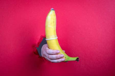 Condom on fresh yellow banana. Red paper background 版權商用圖片