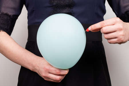 Bloated Stomach. Pain and health problems. Woman with a blue balloon and a needle 版權商用圖片