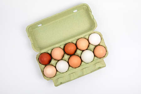 Egg box with organic, free range chicken eggs in different colors. White, brown and dark brown eggs. Food and Easter