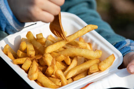 Child eats french fries. Unhealthy food, takeaway and ordering at home