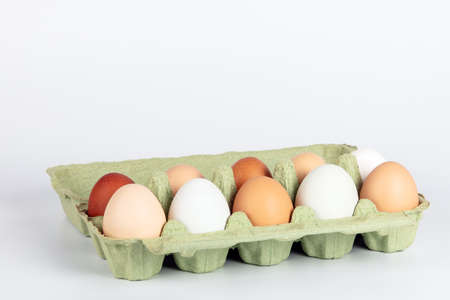 Open egg box with organic, free range chicken eggs in different colors. White, brown and dark brown eggs
