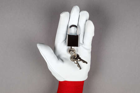 Data security and protection. Hand with leather glove and padlock on a gray background