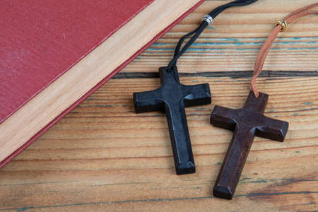 Book and two wooden crosses on a wooden table. Faith, belief and mental health concept