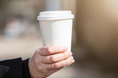 Paper cup with coffee in woman hand. Early morning, breakfast and start of the working da. Blank space for text, mockup
