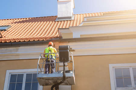Worker repairs the facade of the building. Security cart