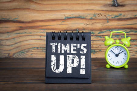 Times Up. Black notebook and green alarm clock on a wooden background