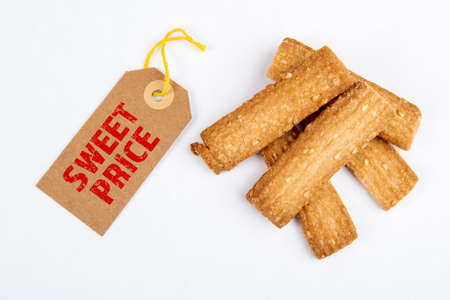 Sweet Price. Sales and marketing concept. Cardboard price tag and cookies on a white background 版權商用圖片