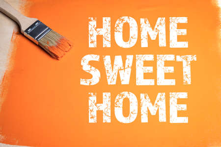 HOME SWEET HOME. Paint brush and orange on a wooden background