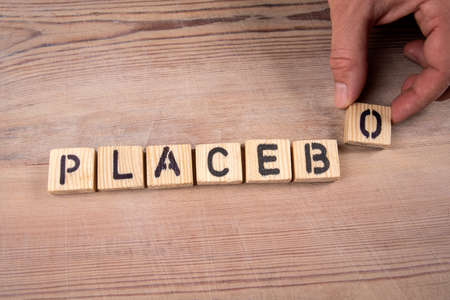 PLACEBO. Wooden alphabet letters and a mans hand on a wooden background