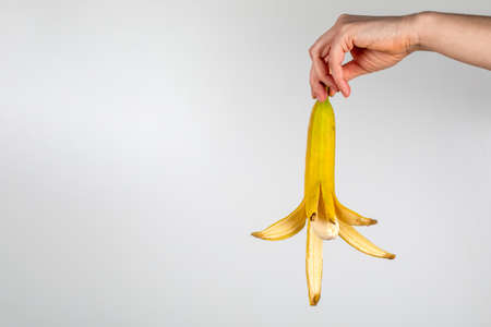 Peeled banana in a womans hand on a white background