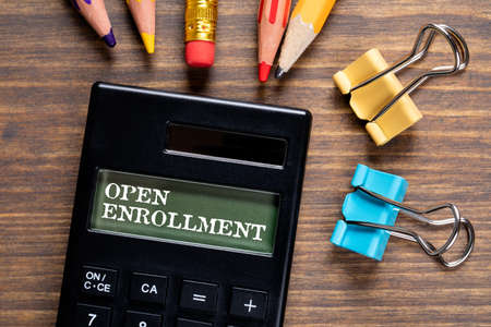 Open Enrollment. Calculator and office supplies on a wooden table