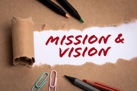 Mission and vision concept. Cardboard paper and pencils on a white background