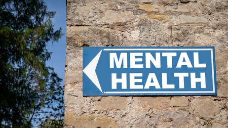 Mental Health concept. Blue directional sign on a dolomite masonry wall