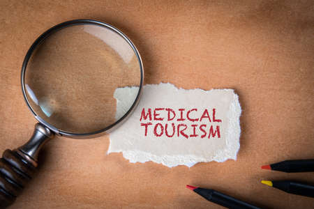 Medical tourism. Colored pencils and a magnifying glass on an orange background