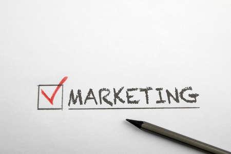Checkmark at the word marketing. Pencil on a white sheet 版權商用圖片