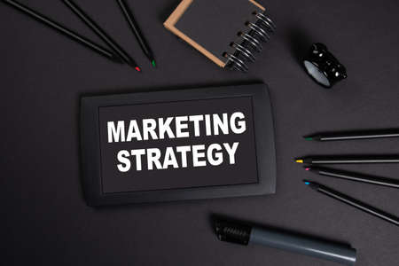 Marketing Strategy. Social media, content and research concept. Tablet on a black office desk
