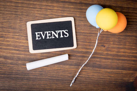 EVENTS. Miniature chalk board and colored balloons on a wooden background