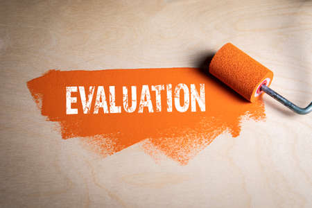 EVALUATION. Paint roller with orange color on a wooden background