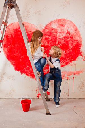 Jungen und Mädchen in Jeans und einem weißen T-Shirt, schauen sich an, mit einem Pinsel und einem Eimer auf einer Leiter die Wand in rot, ein großes Herz malen