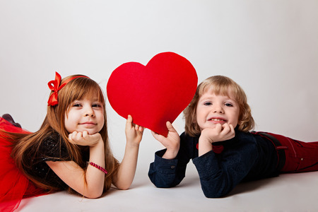 boy and girl lie on a white background holding a red heart Stock fotó