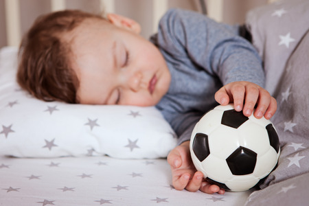 the baby is sleeping in a crib with a football in his hand. football always and everywhere