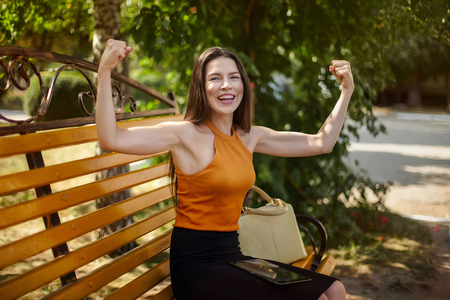 Joyful and happy business woman shows gestures with power. Hands up, sport and business