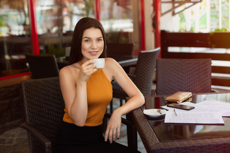 happy business woman drinking coffee with scattered papers on the table. good news, joy and happiness. Banque d'images - 121642459