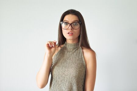 the girl in surprise peers into the frame with glasses. Studio. isolated