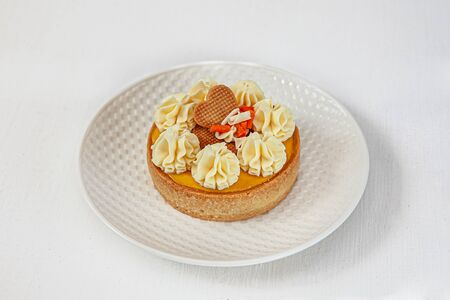 passion fruit cake and mango on top with a round cream On a round white plate on a white background isolated.