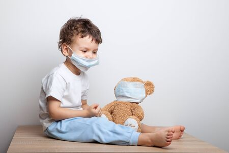 teaching your child preventive measures against viruses and flu. baby, boy in a medical mask puts a medical mask on his teddy bear toy. care for loved ones. Basic hygiene rules. Foto de archivo