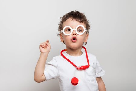 cute and funny curly baby in glasses with a stethoscope, a boy in a doctors suit shows a finger at the viewer. interrogative look. Have you been vaccinated. isolated.