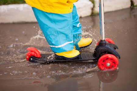 a child in yellow rubber boots and a bright suit rides a scooter through puddles. spray in all directions. hardening, spring. Happy childhood.