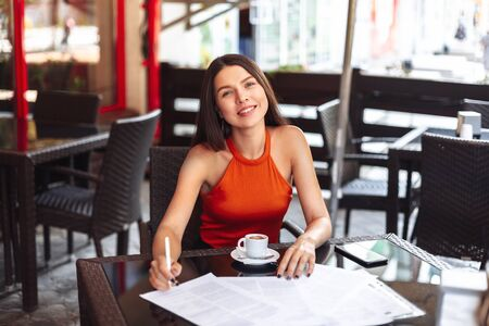happy girl in a cafe over a cup of coffee signs documents. change of life, striving for success and future financial well-being, work in a convenient place.