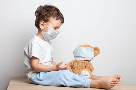 a child in a medical mask put on a respiratory mask for his favorite toy - a teddy bear. spread of coronavirus. hygiene. security measures . health care concept. child protected from the virus.